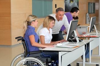 Femme en fauteuil roulant travaillant ans un bureau