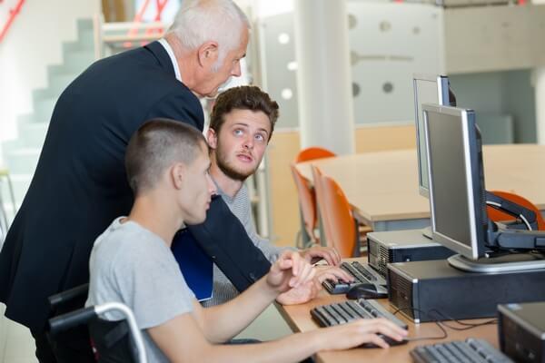 Formateur expliquant à des étudiants devant un écran